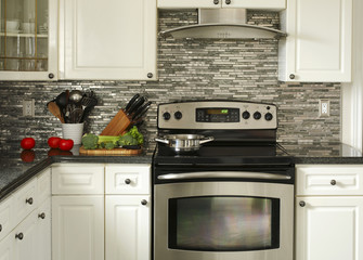 Electric Stainless steel stove, kitchen utensils and vegetables on the cooking table