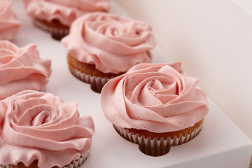 Muffins or cupcakes with flower shaped cream in box, close up view