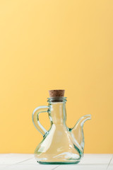 A glass jug with a natural cork on a white-and-yellow background..