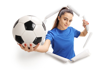 Female soccer player breaking through paper