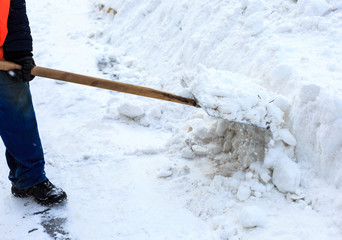Workers sweep snow from road in winter.