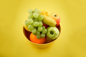 Yellow bowl with fruit stock images. Various fruits on a yellow background. Fruit mix images. Fruit Bowl