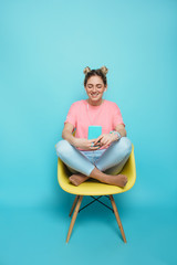 enjoy the music. modern young woman wearing headphones listening to music, sitting on a chair with crossed legs against a blue pastel background