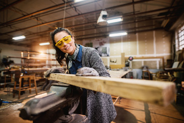 Professional carpenter woman choosing and preparing wood at steel vise in the fabric workshop.