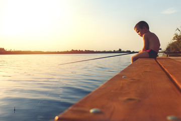 Little boy siting on wooden dock and fishing at sunset.