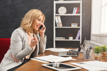 Smiling businesswoman at work talking on phone