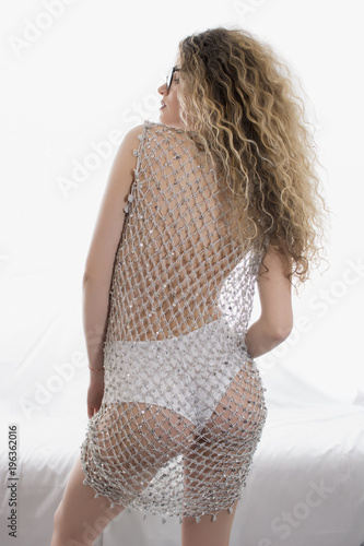 7e7c9ba526b Young girl with curly hair posing in a silver fishnet dress on white  background