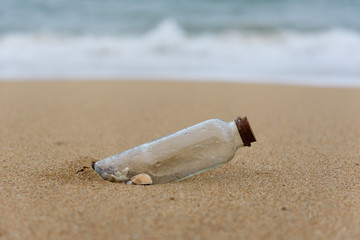 Some shells in a bottle on the beach, shore,cast out by ocean or sea