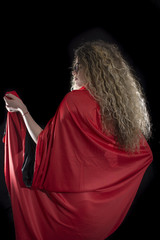 Woman with curly hair dressed in red panties and red cape posing on black background