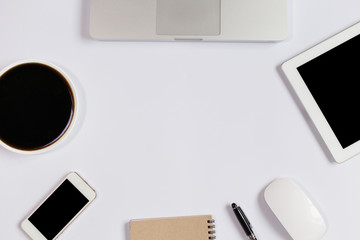 White Office desk table with laptop,smartphone and coffee cup and accessories. Business desk with a keyboard, mouse and pen on white table. Top view of workplace