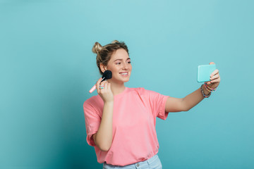 Fashionable young woman, beauty blogger making make-up and live stream for her followers , against a blue pastel background .