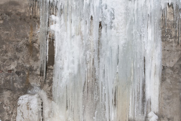 Building wall covered with big icicles. Frozen iced waterfall background