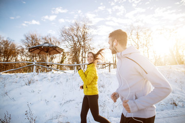 Attractive young woman and man joyfully running in nature on a winter day.