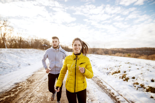 Two sporty cheerful fitness friends running on a winter day in the nature covered in snow.
