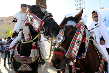 Libyans ride horses as they participate in a street festival held to celebrate their traditional clothing, in Tripoli
