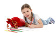 Kleines Mädchen liegt auf dem Boden und schreibt mit Buntstiften Einschulungstüte nebenliegend