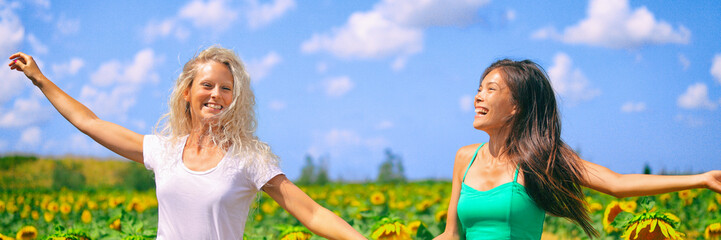 Happy summer girls laughing fun in sunflower field in spring. Cheerful multiracial girlfriends running joyful and smiling in countryside. Asian and Caucasian woman panoramic header. Wall mural
