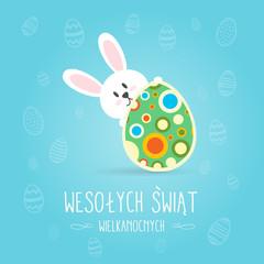 Obraz Koncepcja kartki z życzeniami Wesołych Świąt Wielkanocnych w języku polskim, króliczek trzyma udekorowaną pisankę, w tle motyw świąteczny - fototapety do salonu