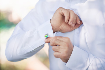 Men's hands button up cuff links on a white shirt. The groom is going to the wedding, dresses close-up.