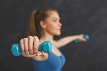 Fitness woman making exercise with dumbbells