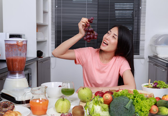 woman eating grape in kitchen room