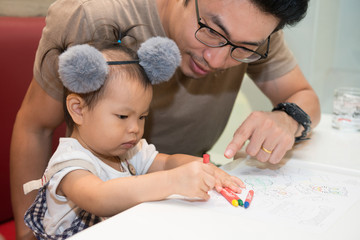 Little baby cute girl painting with crayon with father.
