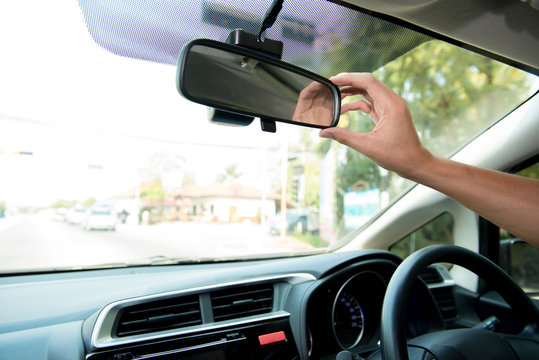 Hand of driver adjust rear view mirror in car for better vision while stop car on the road.