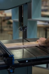 Male carpenter using vertical cutter machine