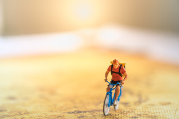 Travel and Sport Concept. Miniature figure of man ride bicycle on map