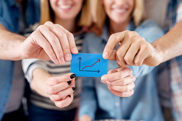 Group of four young motivated people holding together a blue paper with growing business graph.