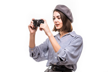 Portrait of a smiling woman wearing beret taking picture with a photo camera isolated over white background