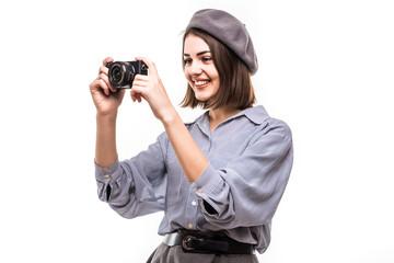 Portrait of an excited woman wearing beret holding photo camera over white background
