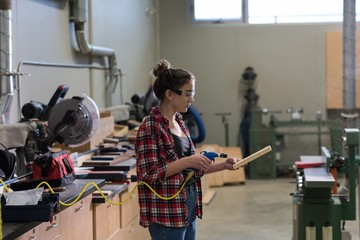 Female young carpenter working in workshop
