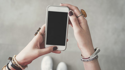 Woman holding empty blank mobile phone