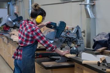 Female carpenter using grinder cutting machine