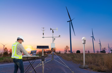 Engineer using laptop computer collect data with meteorological instrument to measure the wind speed, temperature and humidity and solar cell system on wind turbine station, Smart technology concept