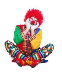 Funny sitting clown in a white studio