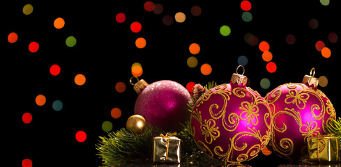 Beautiful pink Christmas balls with patterns, small souvenirs, pine branch on shimmering background