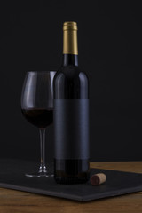 Isolated Red Wine Bottle in a Black, wood Background and Black Label