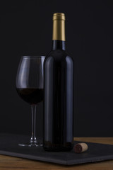 Isolated Red Wine Bottle in a Black, wood Background and no Label