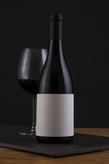 Isolated Red Wine Bottle in a Black, wood Background and White Label