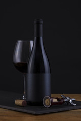Isolated Red Wine Bottle in a Black, wood Background and Black Label and Glass
