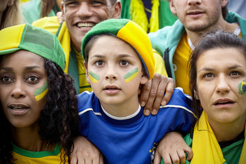 Brazilian football supporters watching match attentively