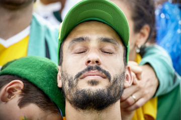 Football fan with head back and eyes closed in disappointment