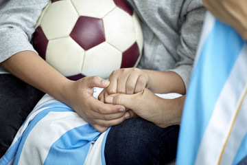 Child with soccer ball holding hands