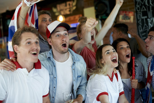 Cheerful soccer fans watching match together in pub