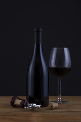 Isolated Red Wine Bottle in a Black Background and Glass