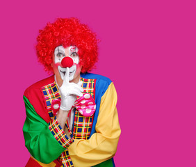 Front view portrait of a clown on pink background speaking in a secret