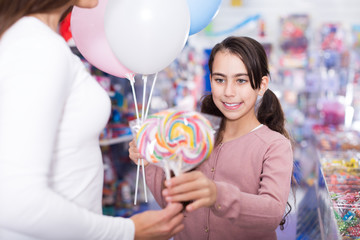 Girl daughter with balloons holding lollipop