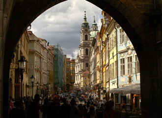 View of the bell tower of the church of St. Nicholas from the arch of the Charles Bridge in Prague